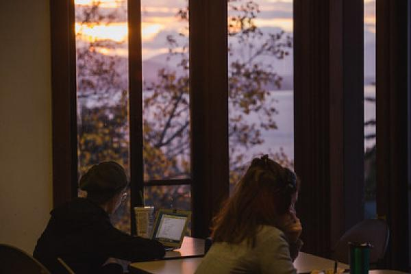people studying near windows at sunset
